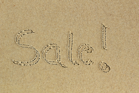 Sale word hand written with exclamation on sand in a beach - a communication message to consumers about discount available on shopping photo
