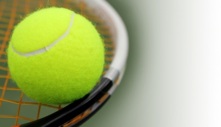 New tennis ball on a new racket with orange string(gut) and the green hard court surface blurred in the background. The photo has copy space for text on the right. photo