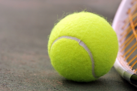 New yellow colored tennis ball placed next to racket(racquet) on synthetic(hard) tennis court surface with copy space for text on the left Stock Photo - 14194346