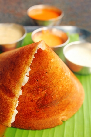 Masala Dosa - Closeup macro photo one of the most popular south indian breakfast served with different types of chutney, sambar and ghee. photo