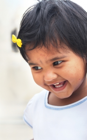Photo of beautiful and blissful indian baby girl with expressive eyes and photogenic face expressing toddlers innocence with a pretty smile. The child is of pre school age and is of indian origin. photo
