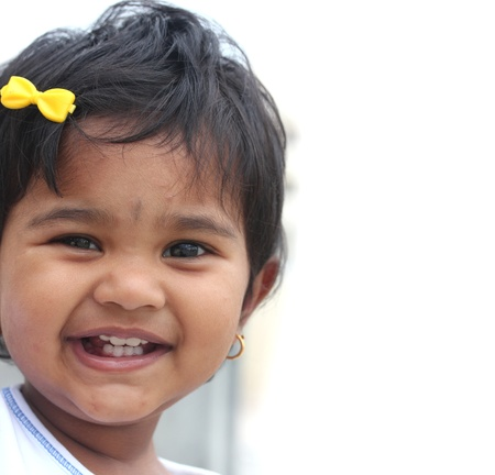 Photo of pretty and happy indian baby girl with expressive eyes and photogenic face expressing toddler's innocence with a beautiful smile. The child is of pre schoolkinder-garten age. photo