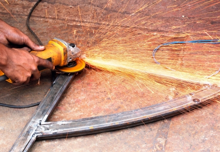 friction: Mechanic using a electrically operated sawing machine to smooth the rough edges of a welded iron bar and sparks flying out because of extreme friction between the machine and the metal