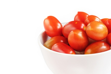 Group of fully ripe organic cherry tomatoes in bright red color arranged in a white melamine bowl on white background Stock Photo - 14325198