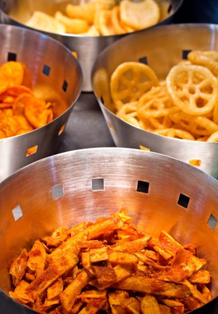 Steel containers with delicious deep fried potato and banana crisps or chips in golden brown colors which are served as side dishes along with main course of meals and as fast food Stock Photo - 14325218