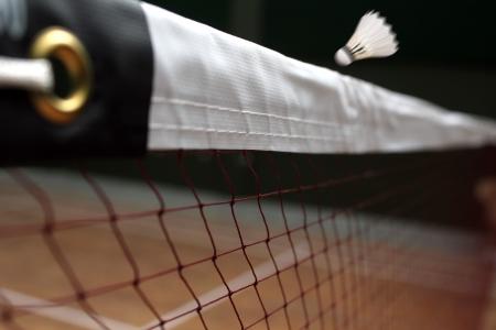 shuttle: Foto van shuttle badminton van dichtbij en een snel bewegend shuttle boven het net in een overdekte badminton Stockfoto