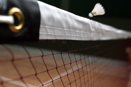 Photo of shuttle badminton net up close and a fast moving shuttlecock above the net in a indoor badminton court