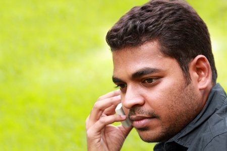 Image of handsome young Indiansouth asian businessman talking and listening on cell phone with copy space for text.  photo