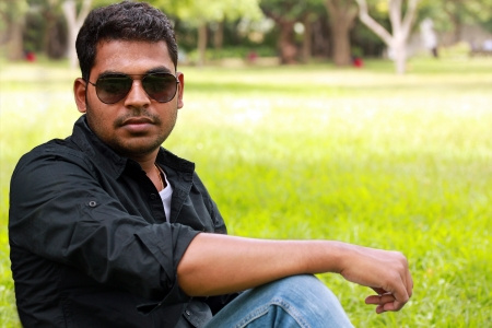 Image of an handsome, stylish, casual and young indiansouth Indian youth with sunglasses looking at the camera in a garden with lawn and trees in the background. photo