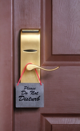 Please do not disturb message, a common request for others not to disturb the motel or resort room occupants, on a paper cardboard tag hung on the door knob of a hotel