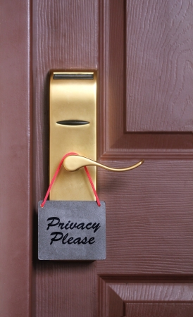 Privacy please words, a common request for others not to disturb the motel or resort room occupants, on a paper cardboard tag hung on the door knob of a hotel photo