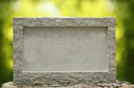 stone tablet: Empty granite signboard with border & frame. The granite is placed in natural outdoor settings showing vibrant green blurred background plants and sunlight effect.   Stock Photo