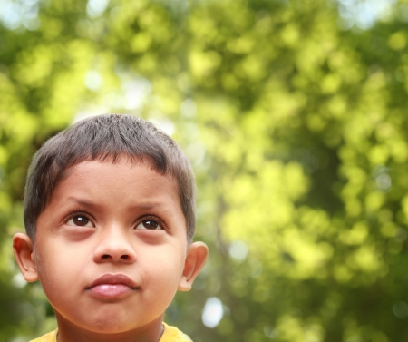 contemplation: Young indian boy of kinder-garten school age thinking or dreaming about playing and having fun after being bored. Background is blurred trees in the backdrop acting as copy-space. Stock Photo