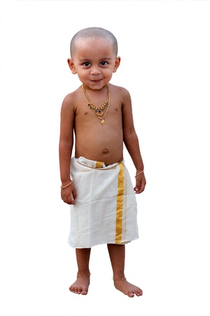 naughty child: Cute and handsome happy indian boy with naughty smile waering traditional south indian(kerala) dress callled mundu and decorated with gold ornaments