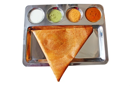 dosa: Appetizing and delicious triangular Indian masala dosa in golden brown color with 3 types of chutney and sambhar served in a steel plate  This thin masala dosa is more popular in chennai and tamilnadu Stock Photo