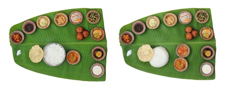 wholesome: Sumptuous and wholesome onam meals called sadhya in kerala. The lunch contains varieties of curries and vegetable mixes along with papad, sweet appam and kheer. The food is served on a banana leaf Stock Photo