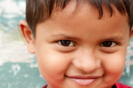 a smiling and cute young asianindian boy looking playfully at the camera and showing expression of being happy and joyful. photo
