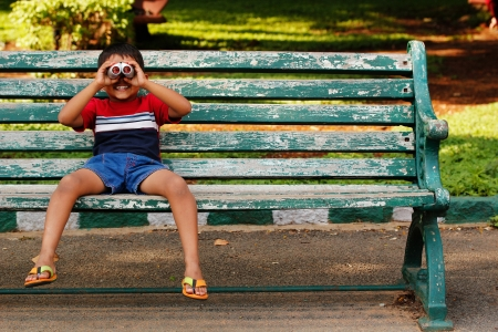 a playful and cute young asianindian boy looking into binoculars and having fun at a park. The child is sitting on a old wooden chair in a garden on a sunny afternoon and having good time. photo