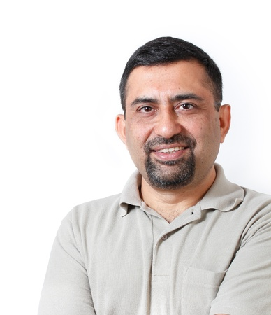 middle aged men: Handsome and happy middle aged mature indian adult business man looking with satisfaction and happiness  The person is wearing t-shirt and  is shot in studio with white background Stock Photo