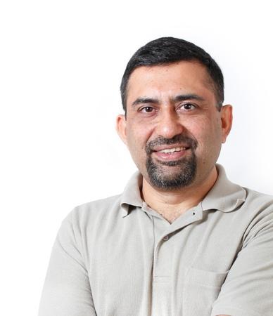 indianin: Przystojny i szczęśliwy średnim wieku dojrzałego indian działalności człowieka dorosłego patrząc z satysfakcją i szczęściem osoba ma na sobie t-shirt i strzał w studio z białym tłem