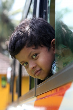 Handsome and cute little indian school kid looking back with happiness from the window of a school bus. The face shows the innocence and childishness of the 6 year old boy with a smile on his face photo