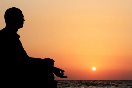 Ein junger Mann sitzt im Lotussitz und meditiert auf einem Strand am Abend mit Sonnenuntergang im Hintergrund. Der Himmel ist orange-gelb und das Meer kann auch in der Meditation Hintergrund gesehen werden