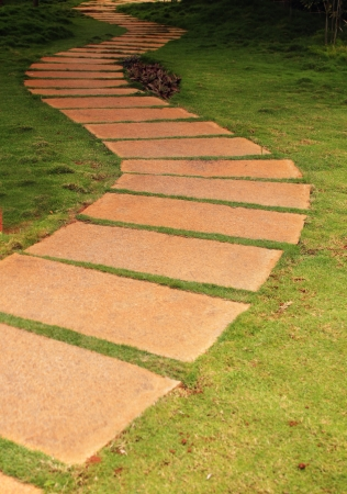 granite park: Walkway formed using granite stone slabs in a garden with lush green grass on either side.