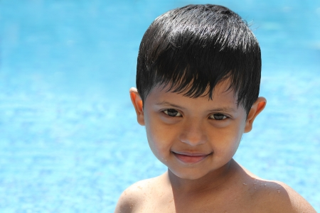 Smiling, happy young preschool Indian kid boy  having fun at summer time in a swimming pool Stock Photo - 16968734