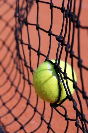 struck:   new tennis ball struck in tennis net on a clay court