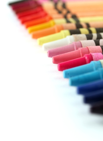 Beautiful colorful pastel crayon  pencils in a row line  on white background with copy space for text photo