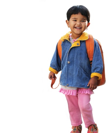 Pretty little indian pre-school girl ready to go to school in very cheerful and happy mood wearing colorful dress with a backpack