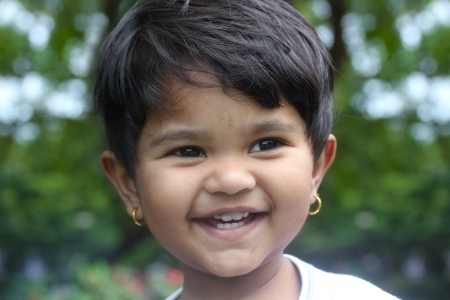 Beautiful young indian girl child smiling &amp, happy and having fun at a outdoor park photo