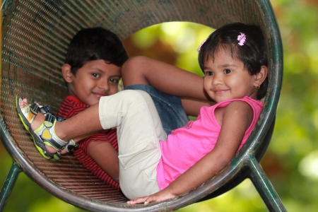 Cute young children boy   girl  playing in tunnel on playground  The photo shows summer time playground with female kid smiling in a tube while the boy in the background looking on