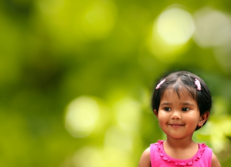 eagerly: pretty young indian girl kid in happy and joyful mood  The photo shows female child tiny tot  smiling and eagerly expecting something interesting
