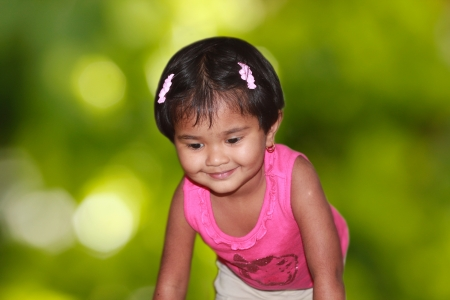playschool: beautiful young girl child happily playing in a park  The photo shows a pretty indian female kid smiling and having fun