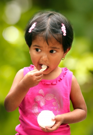 relishing: beautiful young indian girl child enjoying ice cream in a park  The photo shows female kid in pink dress smiling and relishing a scoop of ice cream Stock Photo
