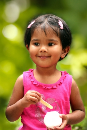 lass: pretty young indian girl kid having fun eating ice cream in a park  The photo shows female child tiny tot  smiling and enjoying her dish