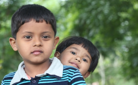 Indian boy & girl(brother and sister) playing & enjoying in a park. This summer time photo is of two beautiful kids sitting together in a garden which is seen in the background