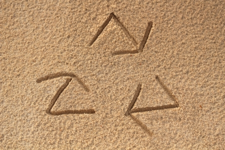 recycle symbol written(drawn) in beach sand - concept photo. This photo shows a recycle sign with three arrows created in sea sand representing concept of saving nature, ecosystem and planet earth photo