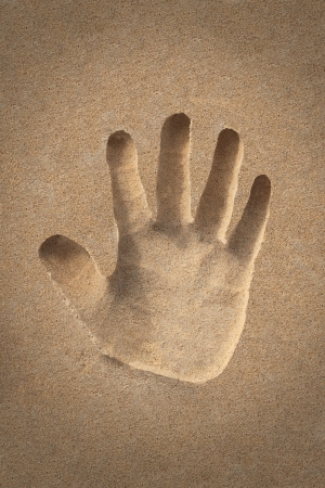 palm(hand) icon or sign creation in beach sand - concept photo. This photo shows a human hand shape created on the sand of a sea shore with all fingers opened photo