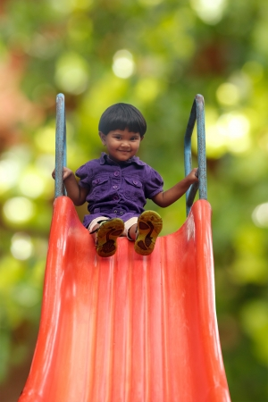 Beautiful & happy indian girl(kid) on park slider on a summer day. This girls photo is on green background with clipping path showing summer time playground & a schoolgirl playing on a slider  photo