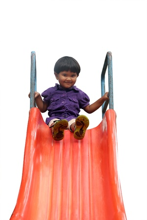 Beautiful cheerful(happy) indian girl(kid) on slider in a summer day. This girls photo isolated on white background with clipping path shows summer time playground & a schoolgirl playing on a slider  photo