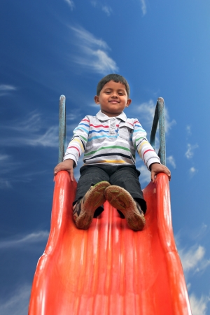 slider: Beautiful smiling(happy) indian boy(kid) on slider in a summer day. This boys photo with sky in the background & clipping path shows summer time playground with a schoolboy playing on a slider