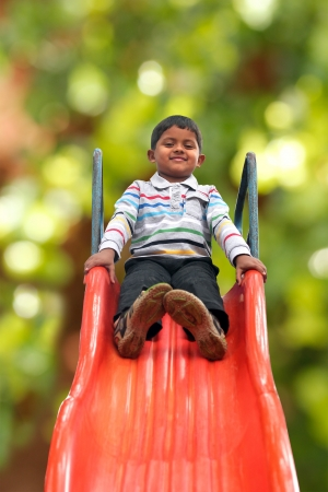 Pretty smiling indian boy(kid) on slider at a park. This boys photo with green background & clipping path shows summer time playground with a schoolboy playing on a slider  photo