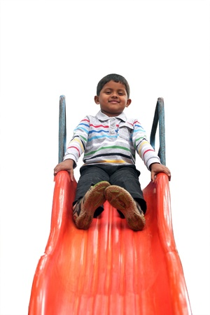 Isolated photo of handsome indian boy(kid) on slider at a park. The isolated photo with white background & clipping path shows summer time playground with a schoolboy playing on a slider  photo
