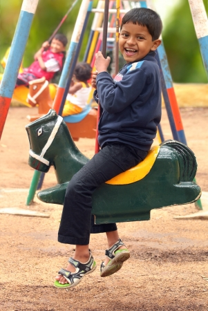 horse laugh: Happy young handsome boy(kid) playing on swing sets in a park. The photo shows summer time playground with a boy and other children swinging and enjoying their leisure time Stock Photo
