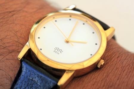 puntualidad: reloj de pulsera de oro moderno que muestra el tiempo como 14:00. Esta foto representa conceptos como la puntualidad, los plazos, la gesti�n del tiempo, etc