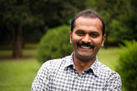 happy, smiling indian male or latin american man. The person can also represent a south asian or a mexican male businessman, executive or employee in positive relaxed mood