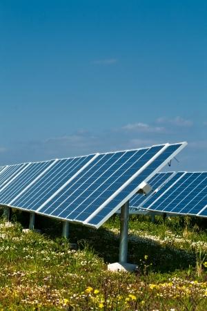 terrena: Una fila di pannelli solari contro un cielo blu in una bellissima campagna