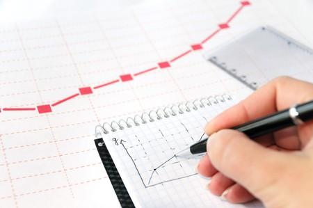 Zakenman analizing een diagram in zijn notitieblok